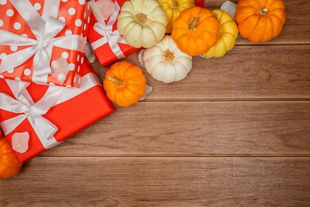 Vista superiore dei concetti di ringraziamento su fondo di legno, zucche, foglie e contenitori di regalo, spazio della copia