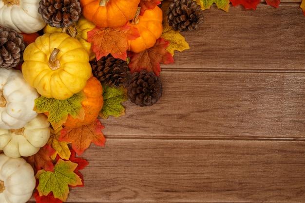 Vista superiore dei concetti di ringraziamento su fondo di legno, zucche, pigna, foglie di acero e spazio della copia