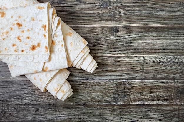 Pane sottile di pita di vista superiore su fondo di legno.