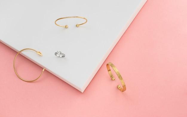 Vista dall'alto di tre braccialetti e anello su sfondo rosa e bianco