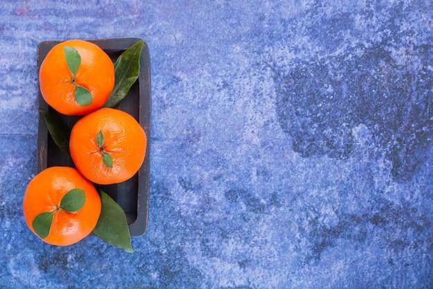 Vista dall'alto di tre mandarini freschi con foglie sul piatto di legno.