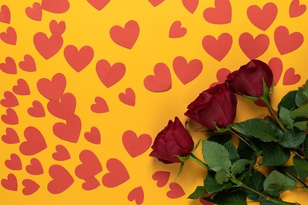La vista dall'alto di tre rose rosse si trova su uno sfondo giallo. molti cuori di cartone