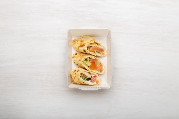 Vista dall'alto tre fette di frittelle con pesce rosso e verdure e formaggio si trovano in una scatola di pranzo su un bianco