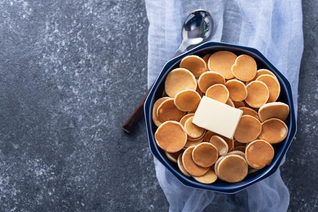 Vista dall'alto minuscole frittelle di cereali con burro nella ciotola blu, cucchiaio su garza blu su grigio