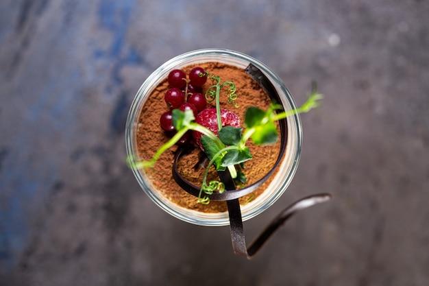 Dessert tiramisù vista dall'alto con frutti di bosco in un bicchiere sul tavolo