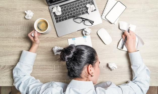 Vista dall'alto di una donna d'affari stanca e sopraffatta, di un impiegato, sdraiata sulla scrivania con laptop, caffè e documenti.