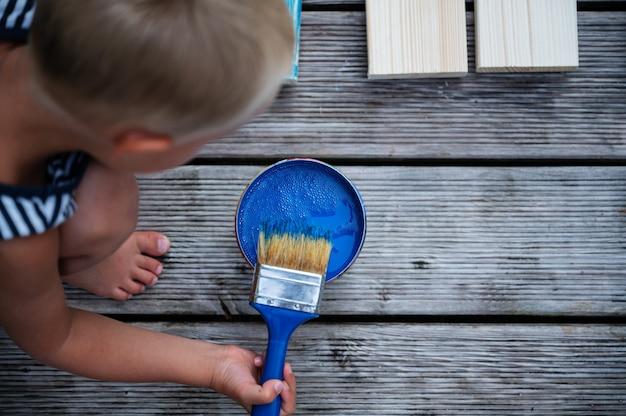 Vista dall'alto del ragazzo del bambino che immerge un pennello in un colore blu brillante per dipingere assi di legno.