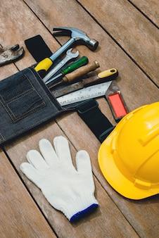 Vista dall'alto della borsa da cintura degli attrezzi e vecchio costruttore di strumenti o ristrutturazione per costruire e riparare la casa su fondo di legno rustico del grunge