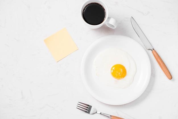 Vista dall'alto della tradizionale colazione veloce e salutare fatta di uova fritte servite su un piatto.