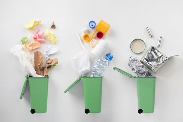 Vista dall'alto di bidoni della spazzatura e immondizia ordinata su grigio, riciclare il concetto