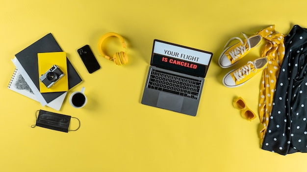 Vista dall'alto degli elementi essenziali di viaggio sulla scrivania su sfondo giallo, concetto di desktop coronavirus.
