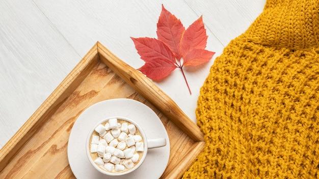 Vista dall'alto del vassoio con una tazza di cioccolata calda con marshmallow e maglione