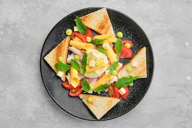 Vista dall'alto di pezzi triangolari di pane tostato, prosciutto, uova sode, cheddar e pomodoro