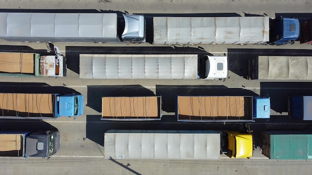 Vista dall'alto sui camion in fila al terminal da vicino. trasporto merci con trattori. trasporto logistico nel parcheggio.