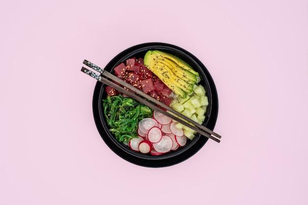 Vista superiore della ciotola del colpo del tonno su fondo rosa Foto Premium