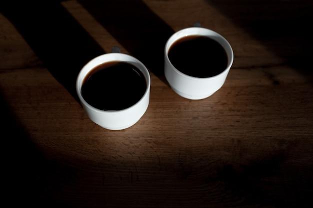 Vista dall'alto di due tazze di caffè sul tavolo di legno.