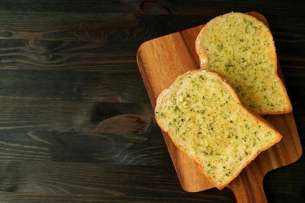 Vista dall'alto di due deliziosi toast fatti in casa al burro all'aglio su breadboard serviti sul tavolo marrone scuro