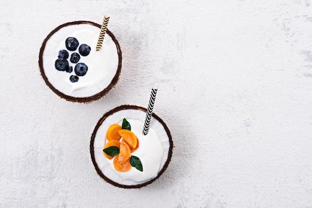 Vista dall'alto due dessert con crema e frutti di bosco in noce di cocco su sfondo bianco con copia spazio, concetto di ciotole di frullato