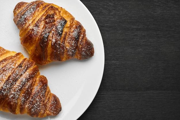 Vista dall'alto su due freschi croissant butirrosi francesi su un piatto bianco su un muro nero con copia spazio