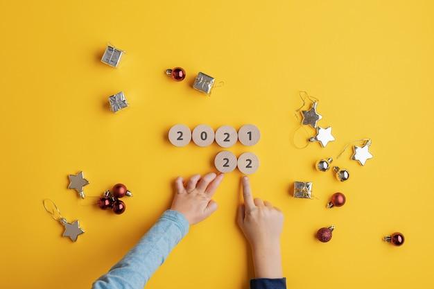 Vista dall'alto di due bambini che cambiano il segno del 2021 fatto di cerchi tagliati in legno in un segno del 2022. su sfondo giallo con decorazioni natalizie sparse in giro.