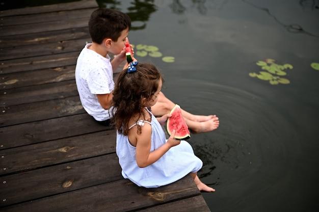 Vista dall'alto di due bambini seduti sul molo, che abbassano i piedi nello stagno con ninfee, si rilassano nella natura, all'aria aperta, mangiano anguria fresca e matura
