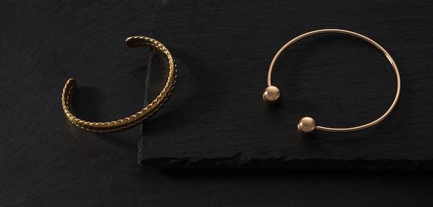 Vista dall'alto di due moderni braccialetti a forma di treccia d'oro su vassoi di pietra nera