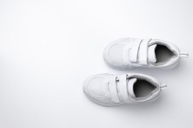 Vista dall'alto di due sneakers bianche per bambini con chiusure in velcro per una calzatura rapida con spazio copia isolato...