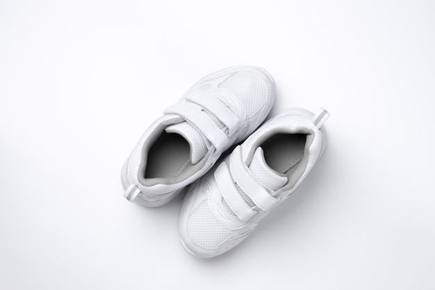 Vista dall'alto due sneakers bianche per adolescenti con velcro situate diagonalmente isolate su uno sfondo bianco