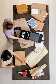 Vista dall'alto di due giovani donne in piedi al tavolo e imballando gli ordini dei clienti tra cartoni, carte e altre cose nell'ufficio del negozio online