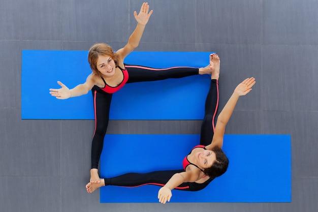 Vista dall'alto di due giovani donne con corpi snelli che si allungano sul tappetino durante le lezioni di fitness