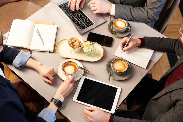 Vista dall'alto di colleghi di lavoro irriconoscibili seduti alla scrivania e bere cappuccino piagnucolare pranzando insieme nel ristorante
