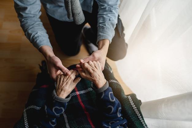 Vista dall'alto irriconoscibile giovane mano nella mano della vecchia. anziani, cura, concetto di famiglia.