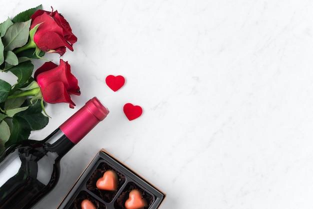 Vista dall'alto del cioccolato di san valentino con rose e vino, concetto di design regalo festivo per appuntamenti speciali.