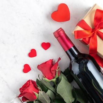 Vista dall'alto del regalo di san valentino con rose e vino, concetto di design festivo per un pasto speciale per le vacanze