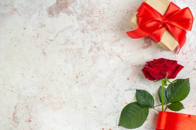 Vista dall'alto regalo di san valentino con rosa rossa su sfondo chiaro coppia amore colore matrimonio sentimento amante cuore spazio libero