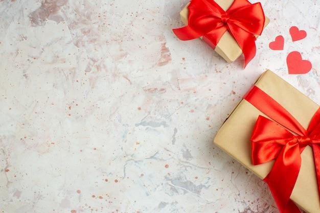 Vista dall'alto regali di san valentino con fiocco rosso su sfondo chiaro amante amore coppia matrimonio cuore colore sensazione spazio libero