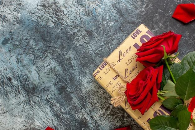 Vista dall'alto regali di san valentino con rose rosse su sfondo grigio coppia matrimonio amore vacanza cuore passione sensazione spazio libero
