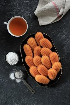 Vista dall'alto madeleine alla vaniglia su piatto in ceramica nera. famosa pasta frolla francese con spolverata di zucchero, servita con tè