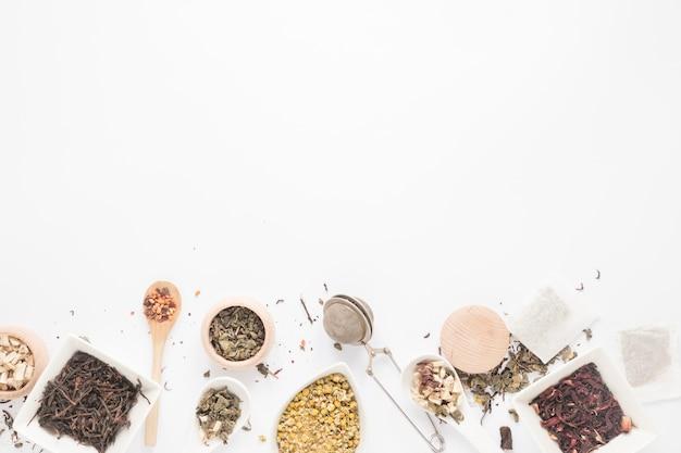 Vista dall'alto della varietà di erbe; cucchiaio; colino da tè; foglie di tè secche disposte su fondo bianco