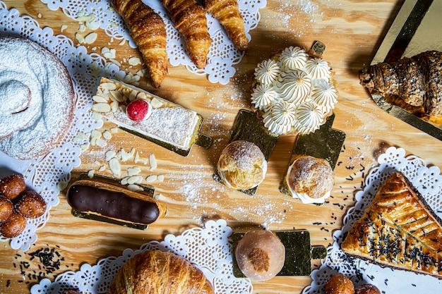 Vista dall'alto di una varietà di torte fatte in casa come crostate, torta al limone, leonesse, mochi, croissant, eclair, dolci e deliziosi.