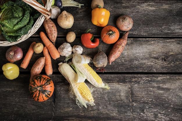 Vista dall'alto di varie verdure autunnali come patata dolce, mais, carote, zucca, cipolle, sparse da un cesto di vimini su assi di legno.
