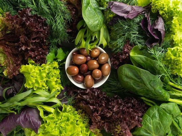 Vista dall'alto: varie erbe fresche commestibili, verdi e viola sono disposte in un cerchio, al centro ci sono le olive verdi