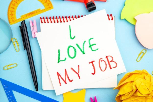 Vista dall'alto vari articoli per ufficio righelli lupa disegno a penna bussola quaderno amo il mio lavoro scritto su carta su sfondo blu