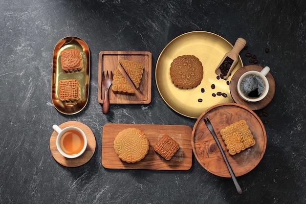 Vista dall'alto varie forme di torta di luna (mooncake) snack da dessert cinese durante il festival di metà autunno del capodanno lunare. concept rustica black asian bakery, servito con tè e caffè. copia spazio