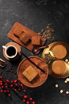 Vista dall'alto varie forme di torta di luna (mooncake) snack da dessert cinese durante il festival di metà autunno del capodanno lunare. concept rustica black asian bakery, servito con tè e caffè