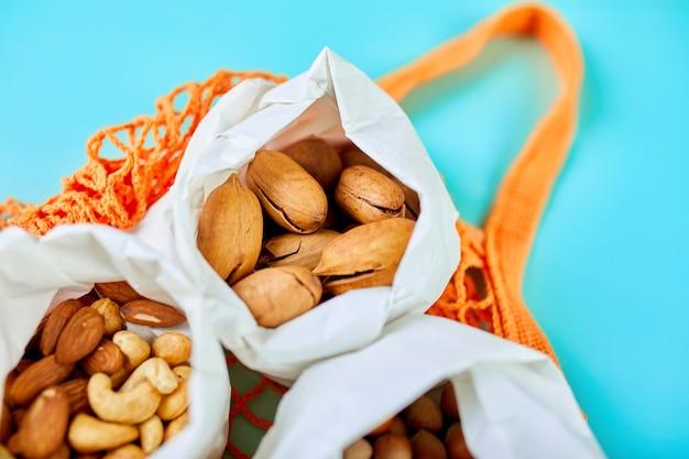 Vista dall'alto di vari tipi di noci sul tavolo in un sacchetto di carta nel sacchetto della spesa sulla superficie blu