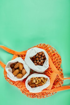 Vista dall'alto di vari tipi di noci sul tavolo in un sacchetto di carta nel sacchetto della spesa sulla superficie verde