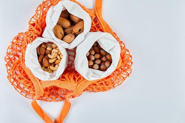 Vista dall'alto di vari tipi di noci sul tavolo in un sacchetto di carta nella borsa della spesa su sfondo bianco, zero waste food shopping. vivere senza sprechi, consegna di noci. copia spazio.