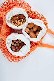 Vista dall'alto di vari tipi di noci sul tavolo in un sacchetto di carta nel sacchetto della spesa sulla superficie bianca