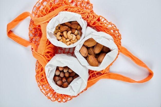 Vista dall'alto di vari tipi di noci sul tavolo in un sacchetto di carta nel sacchetto della spesa